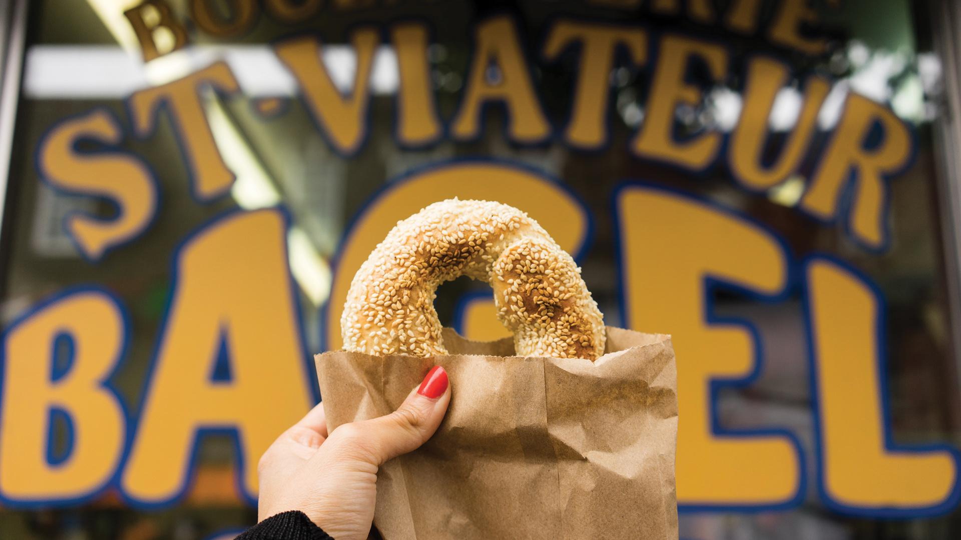 Montreal bagels | A bagel held up outside of St-Viateur Bagel