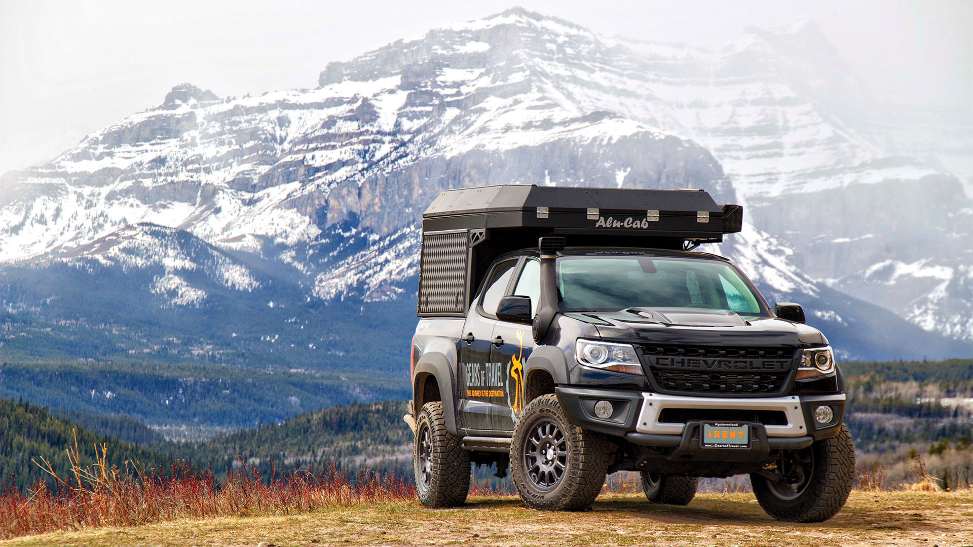 Gears of Travel, Canadian adventure | Chevrolet with canopy camper next to mountains